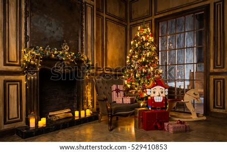 Stock Photo Christmas tree decorated in interior with armchair, nutcracker, presents and wooden horse near fireplace