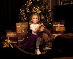Christmas tree decorated with balloons and ornaments in beautiful interior and array of gifts in packaging paper. Small, beautiful, elegant girl is laughing on wooden horse. Holiday, New year