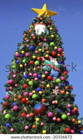 Christmas tree decorated with bright colorful ornaments outside