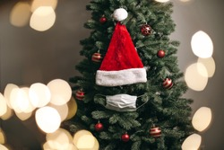 Christmas tree decorated with red balls, medical white masks and a Santa hat. Coronavirus pandemic, quarantine, 2020, 2021. New Year celebration, holiday, self-isolation, stay at home.