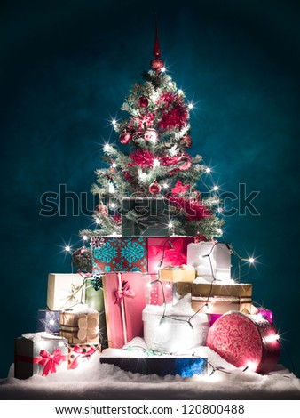 christmas tree decorated with red ornaments and shiny white lights, surrounded by colorful presents covered with snow, in front of blue background with gradient light