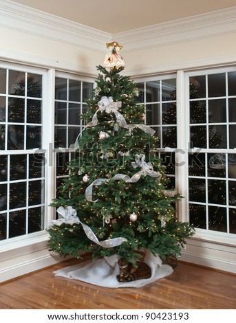 christmas tree decorated with silver and white ribbons and
