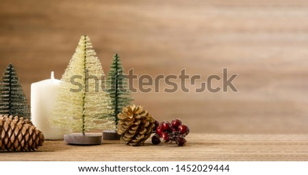 Christmas tree decoration background on wood table with snow.pine cone,mistletoe and bell ball hanging with blur wood wall background.Holiday greeting card banner #1452029444