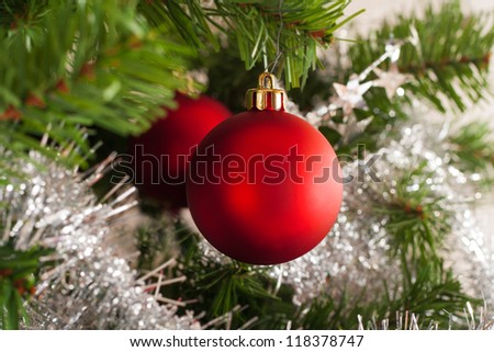Christmas tree decoration on a fir in front of white background.