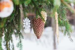 Christmas tree decoration, sparkling gold toy cone, snowflake, ball. Spruce, fir green branch in winter park covered with snow. New Year holiday atmosphere, spirit. Celebration in 2021.