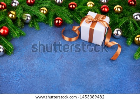 Christmas tree festive border, New Year decorative frame, golden, silver, red balls decorations on green fir branches, white gift box with gold ribbon on blue textured background close up, copy space #1453389482
