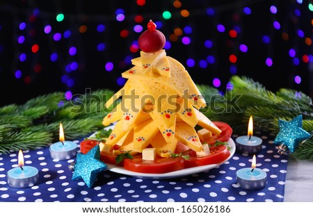 Christmas tree from cheese on table on dark background