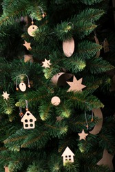 Christmas tree. Green artificial spruce with handmade Christmas decorations. Cardboard decorative stars, small houses and a crescent moon.