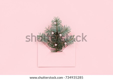 Christmas tree in envelope, minimal New Year`s card. Spruce branch with pearls on pink  background. Holidays, Congratulation concept