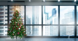 Christmas tree in modern office near big window and building view in city