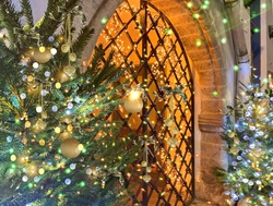Christmas tree in  town ,street  decoration illuminated gold blue light  on medieval street near metal decorative  gate  door  in Tallinn Old town holiday in Estonia
