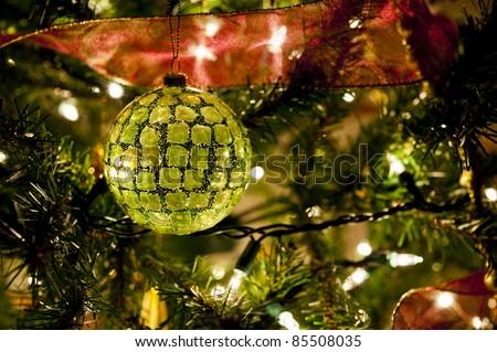 Christmas tree light sparkle illuminating a multi faceted green Christmas ball