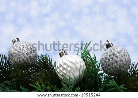 Christmas tree limb with silver glass ball ornaments on snowflake background, Christmas border
