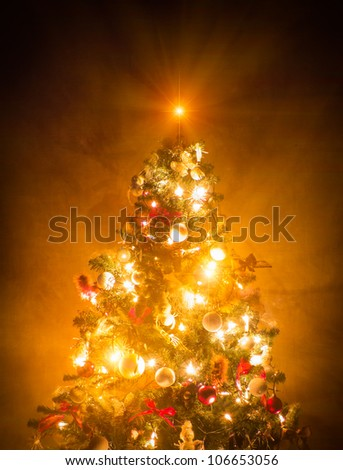 Christmas Tree lit on brown wallpaper