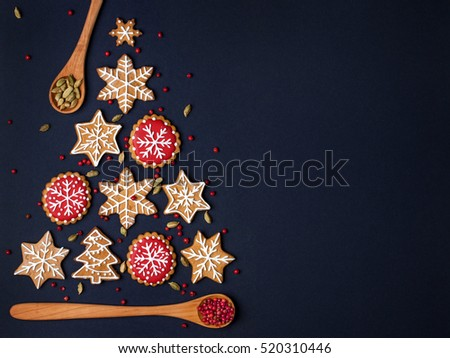 christmas tree made from gingerbread cookies and wooden spoons with spices on dark blue background with copy space for text. holiday, celebration and cooking concept. new year and christmas postcard #520310446