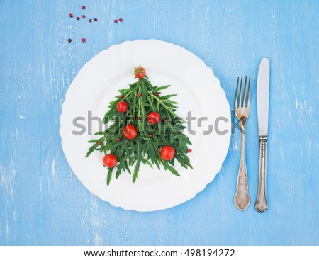 Christmas tree made of arugula and cherry tomatoes on white plate with silverware on blue rustic background. Christmas or New Year background. #498194272