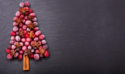 christmas tree made of frozen cranberries, cinnamon sticks and and anise star on dark table, top view with copy space