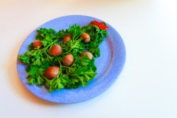 Christmas tree made of herbs and hazelnuts on a plate. New year decor from food. Isolated on a white background. Copy space