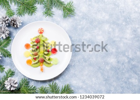 Christmas tree made of kiwi and fruit jelly on a plate with fir branches and decorations. Top view, copy space #1234039072