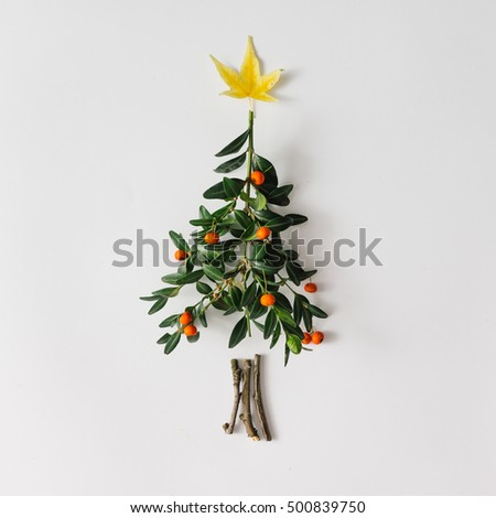 Christmas tree made of leaves and berries. Flat lay. Holiday concept.