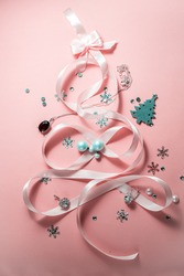 Christmas tree made of ribbon with female accessories on a pink background