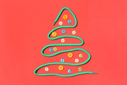 Christmas tree made of shoe lace and different buttons on red background, flat lay