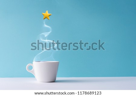 Christmas tree made of steaming coffee or hot drink with yellow star cookie. Winter holiday concept. Minimal New Year background.