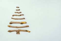 Christmas tree made of wooden branches. Holiday card with pine tree branch. Merry Christmas and Happy New Year Concept. Xmas. Flat lay. Top view. Copy space