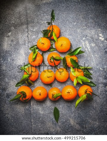 Christmas tree make with tangerines on dark rustic background, top view, festive greeting card