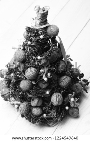 Christmas tree model made of grape branches. Fir tree decorated with nuts, dry anise and acorns. Christmas decorations concept. Cones and dried fruits on little tree on white wooden background #1224549640