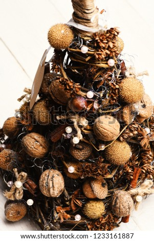 Christmas tree model made of grape branches. Fir tree decorated with nuts, dry anise and acorns. Christmas decorations concept. Cones and dried fruits on little tree on white wooden background #1233161887