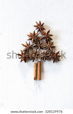 Christmas tree of cinnamon sticks and star anise on white wood