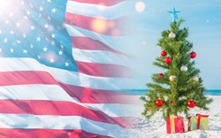Christmas tree on the beach and American flag. Gift Boxes on sand beach shore. White sand like snow. Decorated pine or fir tree. Merry Christmas. Winter vacations. Happy New Year.