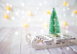 Christmas tree on the toy sled. Christmas and new year card on wooden background