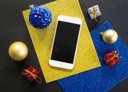 Christmas tree ornament and smartphone flat composition. White smartphone with black screen on table. Christmas or New Year mockup with personal gadget. Smartphone template with winter holiday decor