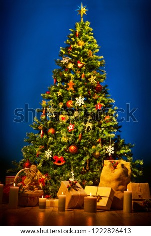 Christmas Tree over Blue Background, New Year Decorations Hanging on Chritmastree, Present Gifts and Bag #1222826413