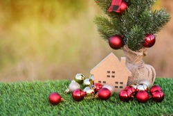 Christmas tree, red christmas ball and small wooden house on a green grass in the morning garden