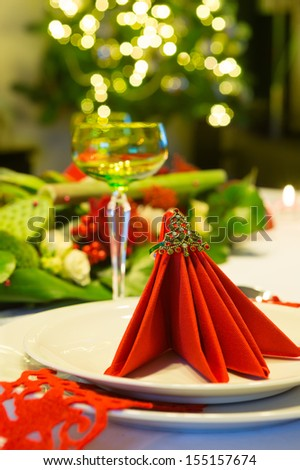 Christmas tree shining behind a decorated christmas dinner table with red napkins