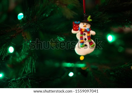 Christmas tree snowman ornament with defocused lights background #1559097041