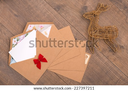Christmas tree toys and  decoration like envelopes with red bows  with white clear sheet s of paper  and wicker  iron deer  on wooden table top view