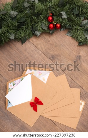 Christmas tree toys and  decoration like envelopes with red bows  with white clear sheet s of paper  and fir branch on wooden table top view  with copy place