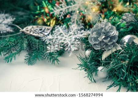 Christmas tree toys berry balls hanging on Christmas tree on light background with ribbon from Christmas tree. Copy space, background. Copy space
