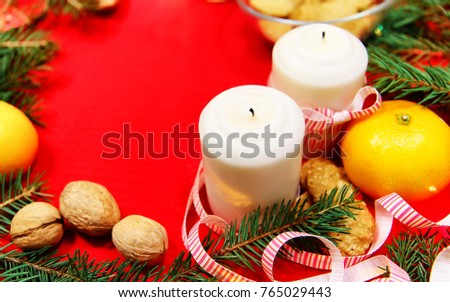Stock Photo Christmas tree toys on red napkin. Mandarins and candles on the table. A fur-tree branch and fruit on a New Year's table.