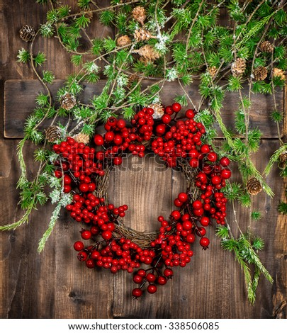 Christmas tree twigs and red berries wreath on wooden texture advent