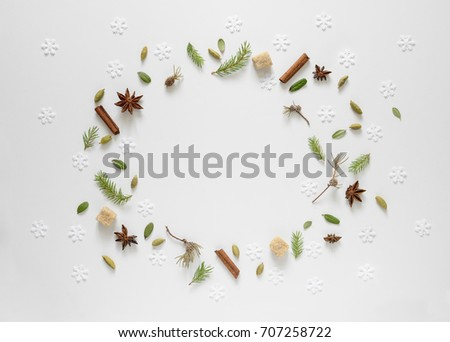 Christmas tree twigs, cardamom seeds and anise stars, fallen leaves and snowflakes to remind how cozy home smells when winter comes and it's cold outside, flat lay background with a space for a text #707258722