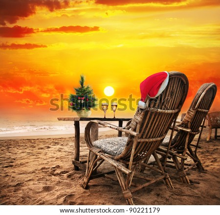 Christmas tree, Two glasses of champagne and Christmas hat on the chair on the beach with view to the ocean  and orange sunset sky in Goa, India