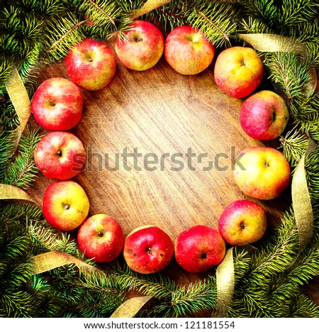 christmas  tree with  apples and decorations on a wooden board/Christmas card design featuring a home made christmas wreath  on a rustic wooden wall /holidays background