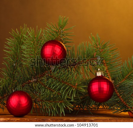 Christmas tree with beautiful New Year's balls on wooden table on brown background - stock photo
