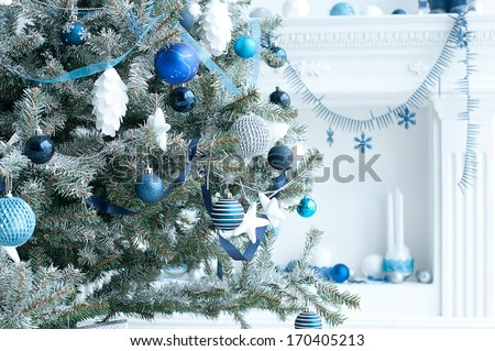 Christmas tree with blue and white toys in the interior / Christmas card with white and blue decor