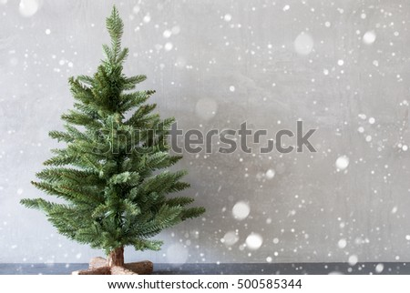 Photo of Christmas Tree With Cement Wall As Background, Copy Space, Snowflakes
